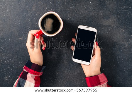 Female hands holding coffee cup and white mobile phone over dark table - stock photo