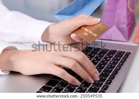 Female hands holding credit card with laptop and paper bags on table on bright background - stock photo