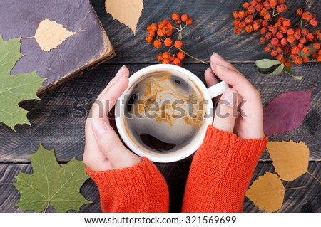 Female hands holding cup of coffee on autumn wooden background. Old book, autumn leaves and dried rowan on background. Concept cozy coffee cup. Top view - stock photo