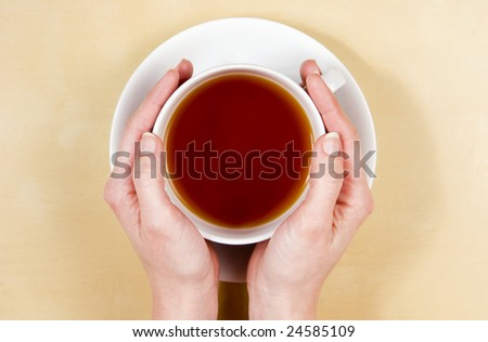 female hands holding cup of tea on light wood table - similar more at my portfolio
