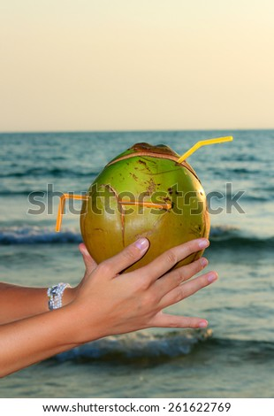 Female hands holding cut coconut on sea background at sunset view 1 - stock photo