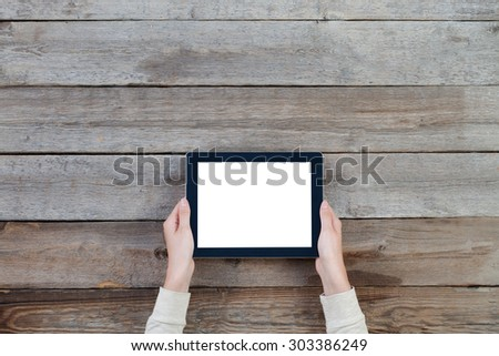 female hands holding digital tablet computer with isolated screen over old grey wooden background table. - stock photo