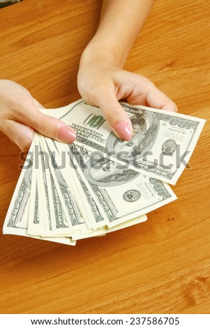 Female hands holding dollars, closeup - stock photo
