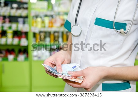 Female hands holding euros banknotes at the pharmacy