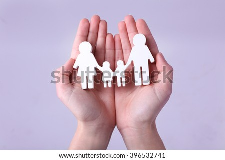 Female hands holding family figure on grey background