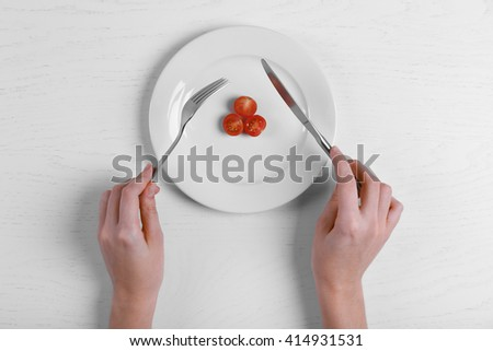 Female hands holding fork and knife on a plate with cherry tomatoes on white table. - stock photo