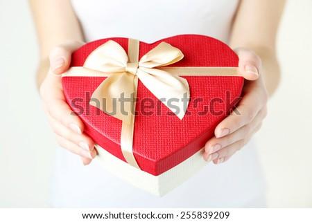 Female hands holding heart gift box - stock photo