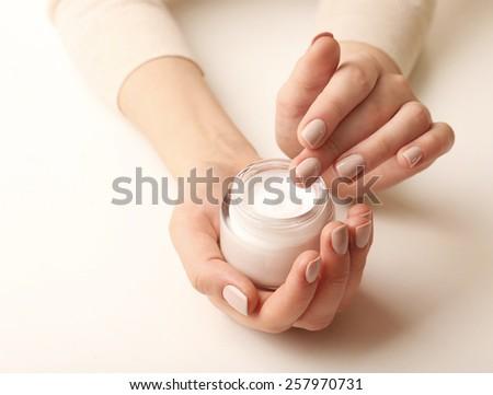Female hands holding jar of cream isolated on white - stock photo