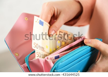 Female hands holding leather purse with euro banknotes closeup - stock photo