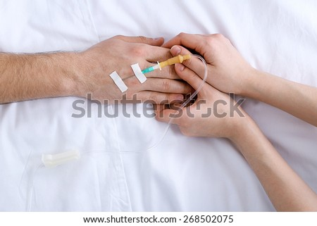Female hands holding man hand with dropper needle on bed close-up - stock photo
