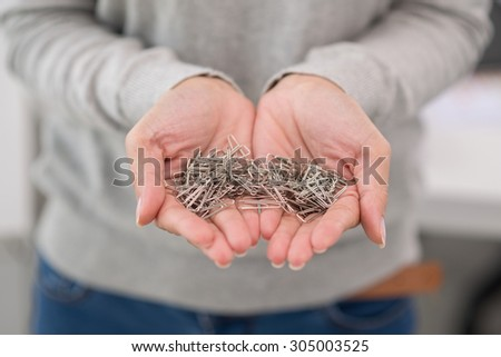 Female hands holding many paper clips, selective focus