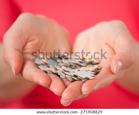 Female hands holding many puzzles - closeup shot - stock photo