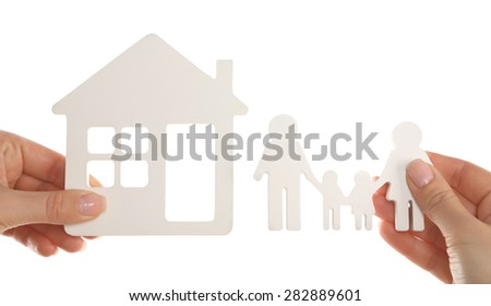 Female hands holding model of house and paper family isolated on white - stock photo