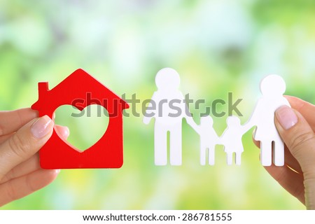Female hands holding model of house and paper family on bright background - stock photo