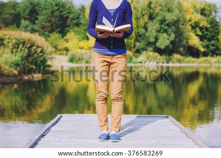 female hands holding open book. Reading concept background - stock photo