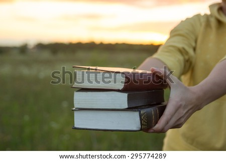 Female hands holding opened hardback book, diary with fanned pages on blurred nature landscape background against sunset sky with back light. Copy space, back to school education concept.  - stock photo