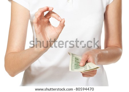 Female hands holding pack of money and showing OK sign, shallow deep of fields, focus on the OK sign - stock photo