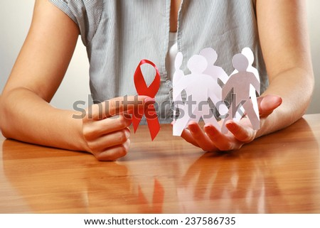 Female hands holding paper people and a red hiv ribbon, closeup - stock photo