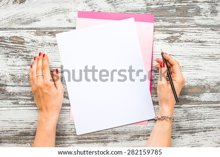 Female hands holding pen and blank paper sheets with copyspace on old wooden table. Top view - stock photo