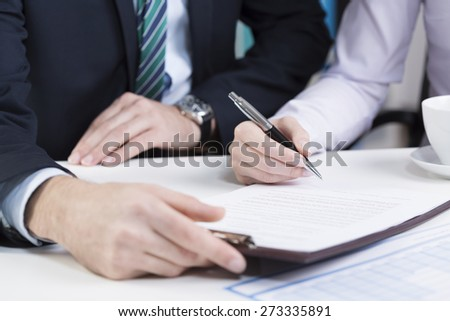 Female hands holding pen and signing contract - stock photo