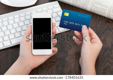 female hands holding phone and credit card over the table with the keyboard in office - stock photo