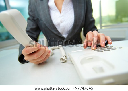 Female hands holding phone receiver and dialing number - stock photo