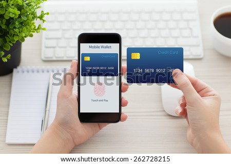 female hands holding phone with app mobile wallet and fingerprint for online shopping and credit card over the desk in the office - stock photo