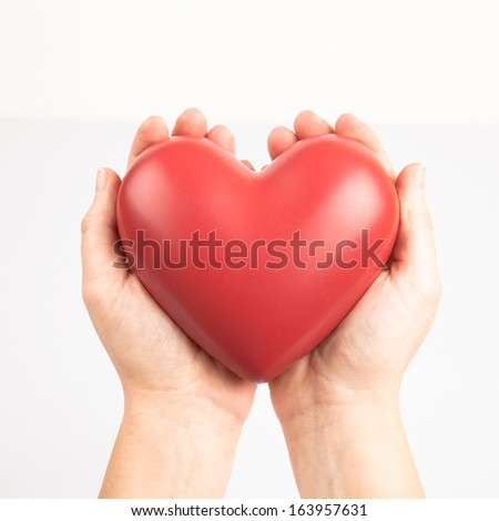 Female hands holding red heart - stock photo