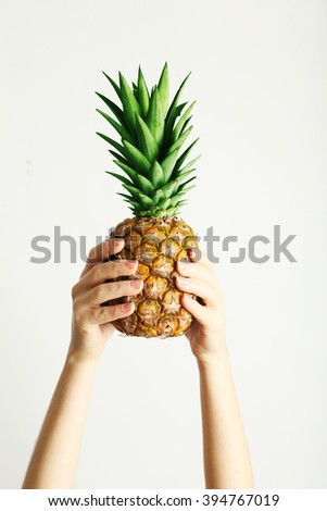 Female hands holding ripe pineapple on a white background - stock photo