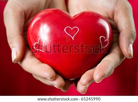 Female hands holding shiny heart - stock photo