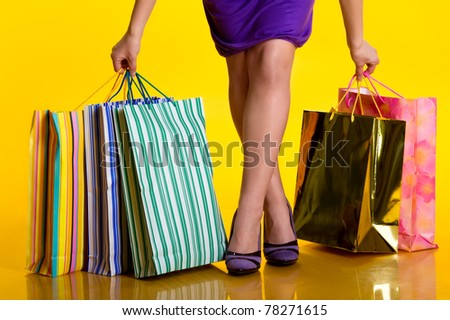 Female hands holding shopping bags - stock photo