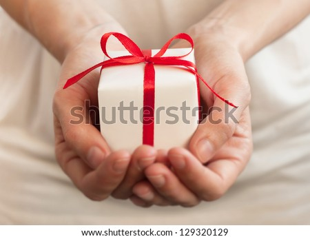 Female hands holding small gift with ribbon. - stock photo
