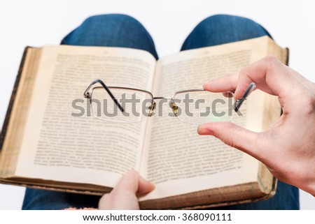 Female hands holding spectacles above the book on her knees. First-person view.