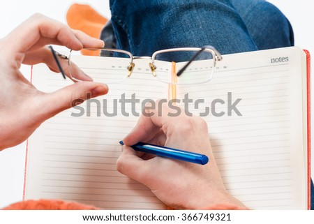 Female hands holding spectacles above the notepad on her knees. First-person view.