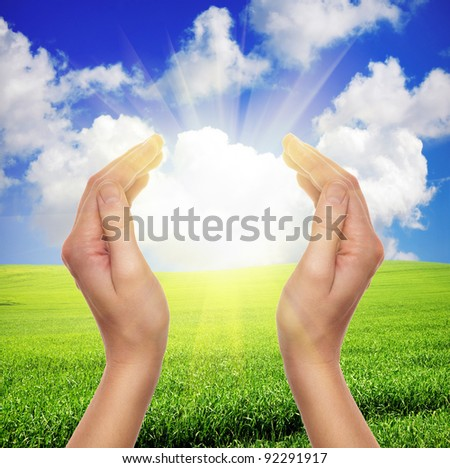 female hands holding sun over green field of grass and blue sky - religion and environment concept - stock photo