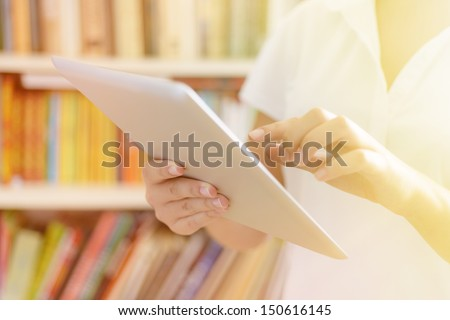 Female hands, holding tablet computer, bookshelves at background - library or college class or hospital interior, bright warm sunlight effect. - stock photo