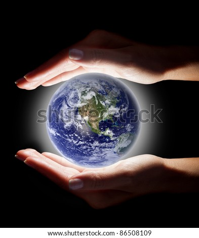 Female hands holding the world - over a dark background