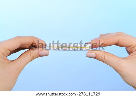 Female hands holding thermometer on blue background