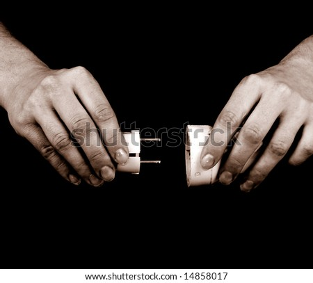 female hands holding two electrical plugs - stock photo