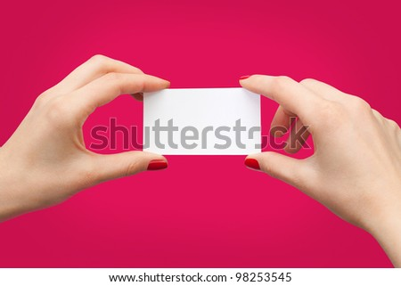 female hands holding white business card on red background.