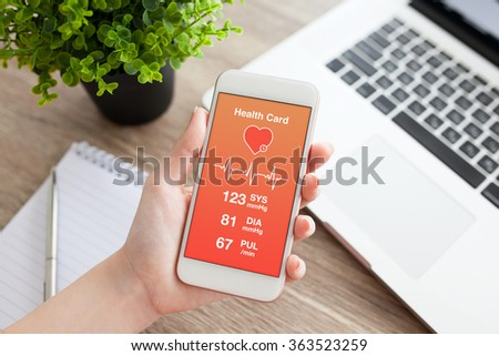 female hands holding white phone with health card on the screen and pen with notebook - stock photo