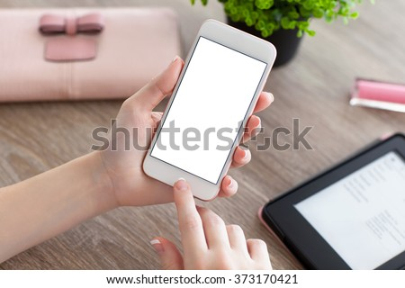 female hands holding white phone with isolated screen and e-rider on the women table - stock photo