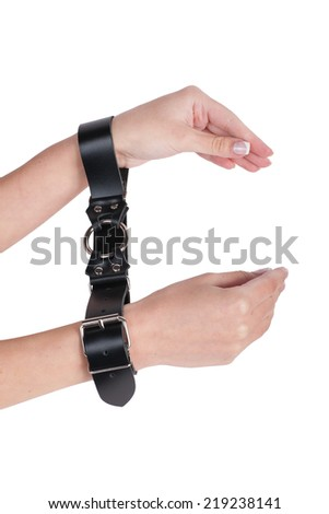 female hands in black leather handcuffs on white background - stock photo