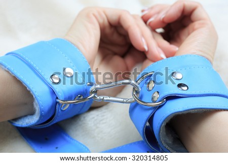 female hands in blue leather handcuffs. eagerly grabbed the sheets.. sex toys. - stock photo