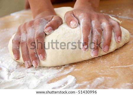 female hands in flour closeup kneading dough on table - stock photo