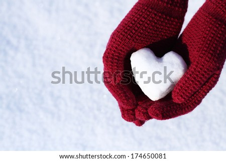 Female hands in knitted mittens with a vintage romantic red heart on white snow background. Love concept. Valentine's Day Greeting card with copyspace. Valentine background.  - stock photo
