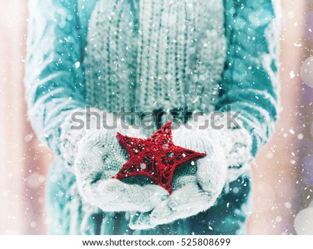 Female hands in light teal knitted mittens with entwined red star on a white snow background. Winter and Christmas cozy concept