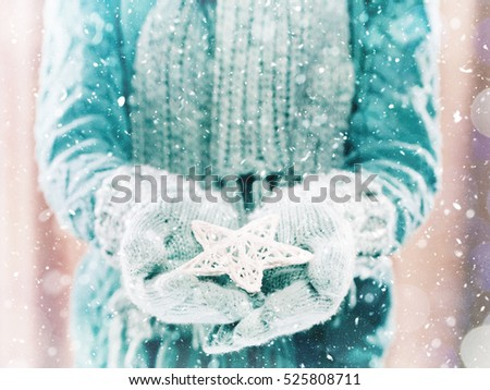 Female hands in light teal knitted mittens with entwined white star on a white snow background. Winter and Christmas cozy concept