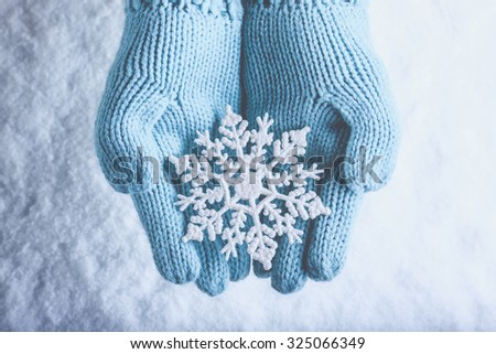 Female hands in light teal knitted mittens with sparkling wonderful snowflake on a white snow background. Winter and Christmas cozy concept. - stock photo
