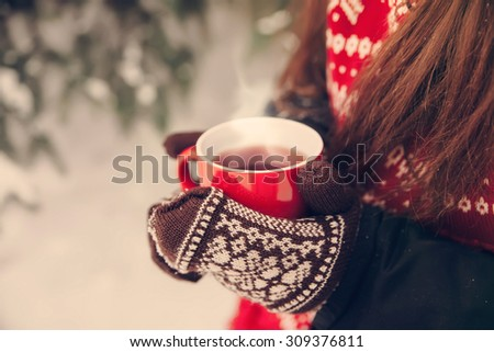 female hands in mittens holding a cup of tea, closeup outdoors - stock photo